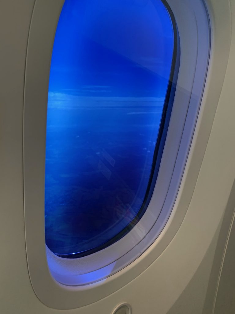 oval-shaped airplane window with view of blue sky
