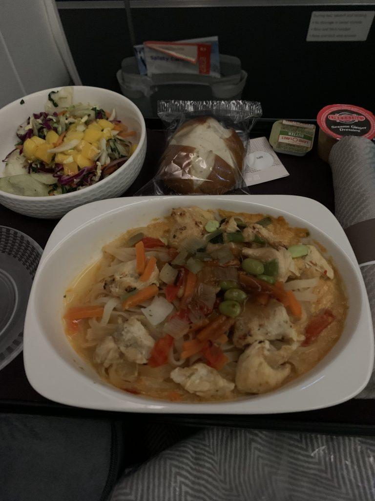 meal on airplance, chicken dish, pretzel rolls, salad